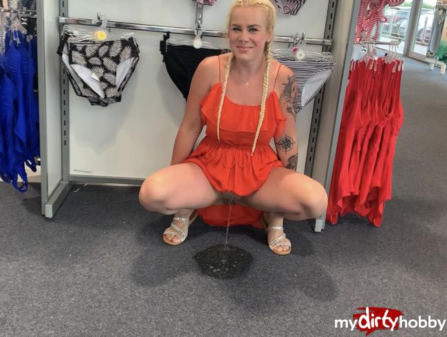 Public im Fashionshop - vor dem Bikini Ständer einfach auf dem Boden gepisst - ups ist der Teppich n